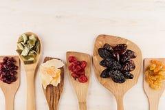 Assortiment van droge vruchten op houten lepels op witte achtergrond Stock Fotografie