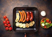Assortiment van geroosterde worsten en groenten in grillpan Royalty-vrije Stock Foto's