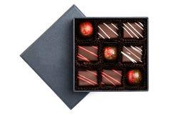 Assortiment van luxebonbons met redlplonsen in zwarte doos op witte achtergrond worden geïsoleerd die stock foto