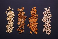 Assortiment van noten op een zwarte achtergrond - gezonde snack Stock Afbeeldingen