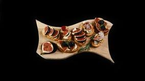 Assortiment van snacks aan wijn met fig., kaas, honing en okkernoten op geroosterd knapperig brood op een houten die raad op zwar stock foto