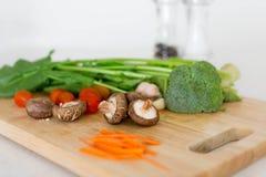 Assortiment van verse kleurrijke die groenten op een houten scherpe raad worden geplaatst Stock Afbeeldingen
