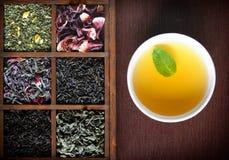 Assortimento asciutto del tè in scatola di legno con la tazza bianca Immagini Stock Libere da Diritti
