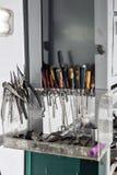 Assortimento degli attrezzi di fai-da-te che appendono in un armadietto contro una parete olio per motori sporco Immagine Stock Libera da Diritti