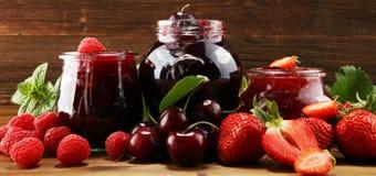 Assortimento degli inceppamenti, delle bacche stagionali, della ciliegia, della menta e dei frutti in barattolo di vetro immagine stock