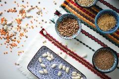 Assortimento dei cereali, dei fagioli e delle lenticchie in ciotole ceramiche turche tradizionali sulla tovaglia luminosa Immagine Stock