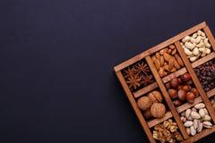 Assortimento dei dadi in una scatola di legno su un fondo nero - spuntino sano Immagini Stock Libere da Diritti