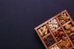 Assortimento dei dadi in una scatola di legno su un fondo nero - spuntino sano immagini stock