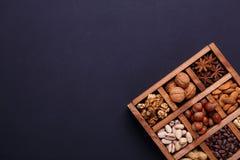 Assortimento dei dadi in una scatola di legno su un fondo nero - spuntino sano immagine stock