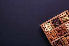 Assortimento dei dadi in una scatola di legno su un fondo nero - spuntino sano fotografie stock libere da diritti