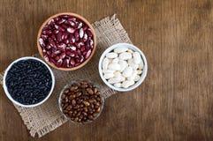 Assortimento dei fagioli crudi variopinti in ciotole su una tavola di legno Alimento sano, stante a dieta, concetto di nutrizione immagine stock
