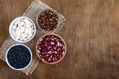 Assortimento dei fagioli crudi variopinti in ciotole su una tavola di legno Alimento sano, stante a dieta, concetto di nutrizione immagini stock