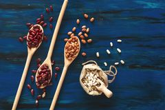 Assortimento dei fagioli in cucchiaio di legno sulla b di legno blu scuro immagine stock libera da diritti
