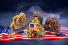 Assortimento dei germogli, del petrolio e della bandiera americana della cannabis - medica del veterano Fotografie Stock