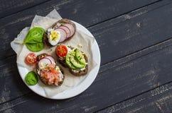 Assortimento dei panini - panini con formaggio, il ravanello, il cetriolo, l'uovo di quaglia, l'avocado ed il salmone affumicato Fotografia Stock