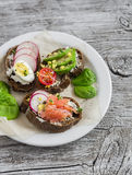 Assortimento dei panini - panini con formaggio, il ravanello, il cetriolo, l'uovo di quaglia, l'avocado ed il salmone affumicato Immagini Stock
