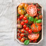 Assortimento dei pomodori rossi dell'agricoltore organico maturo su una tavola Immagine Stock