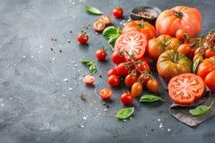 Assortimento dei pomodori rossi dell'agricoltore organico maturo su una tavola Fotografie Stock