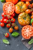Assortimento dei pomodori rossi dell'agricoltore organico maturo su una tavola Fotografie Stock Libere da Diritti