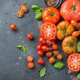 Assortimento dei pomodori rossi dell'agricoltore organico maturo su una tavola Fotografia Stock Libera da Diritti