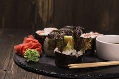 Assortimento dei rotoli di sushi con il salmone e le verdure Fotografia Stock