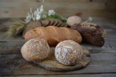 Assortimento del pane di segale e del grano e del panino, primo piano su un fondo rustico di legno fotografie stock libere da diritti