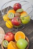 Assortimento del primo piano esotico di frutti: kiwi, mela rossa e verde, arance e limone sulla tavola di legno Immagini Stock