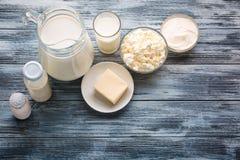 Assortimento della drogheria dei prodotti lattier-caseario sulla tavola di legno rustica Immagine Stock