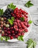 Assortimento delle bacche - lamponi, uva spina, ribes rosso, ciliege, ribes nero su un piatto bianco su un woode rustico leggero Immagine Stock Libera da Diritti