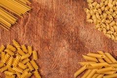 Assortimento delle paste differenti di forma su fondo di legno Immagine Stock