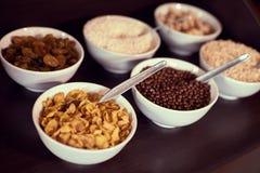 Assortimento di cereale da prima colazione e di frutta secca differenti sulla tavola di legno Immagini Stock