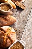 Assortimento di pane al forno sul fondo di legno della tavola Immagini Stock