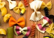 Assortimento di pasta variopinta su fondo di legno, alimento italiano Fotografie Stock