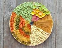 Assortimento di pasta variopinta su un vassoio rotondo Tinto con naturale Immagini Stock Libere da Diritti