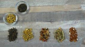 Assortimento/varietà del tè liberamente in vetro ad ora del the di legno del fondo immagine stock libera da diritti