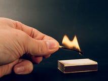 Assortissez avec une flamme du feu brûlant être tenu par une main photos stock