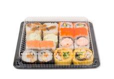 Assortisushi in open plastic die doos worden op witte achtergrond wordt geïsoleerd geplaatst die Royalty-vrije Stock Foto's