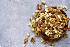 Assortmen von Nüssen in einer hölzernen Schüssel - gesunder Snack Draufsicht mit Stockfoto
