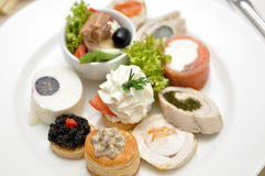 Assortment of aperitif. On a white plate, with cheese, fish, caviar, olives stock photography