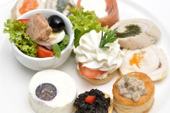 Assortment of aperitif. On a white plate, with cheese, fish, caviar, olives stock images