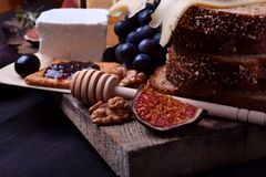Assortment of appetizers: different sorts of cheese, crackers, grapes, nuts, olive marmalade, figs and olives. Against the dark background royalty free stock photography