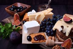 Assortment of appetizers: different sorts of cheese, crackers, grapes, nuts, olive marmalade, figs and olives. Against the dark background royalty free stock image