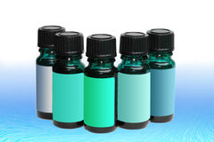 Assortment of aromatherapy bottles with blank labels in shades Royalty Free Stock Photography