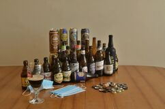 Assortment of artisan beer bottles and cans on table. Drinking at home in pandemic times