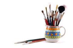Assortment of artistic brushes. Variety of artistic brushes in an vintage pitcher on a white background Stock Photos