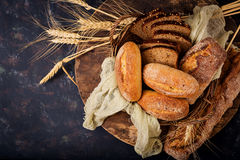 Assortment of baked bread and bun on a wooden background. Stock Image