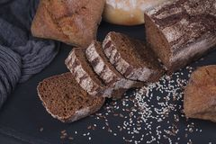 Assortment of baked bread on dark background. stock photography