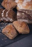 Assortment of baked bread on dark background. royalty free stock photography