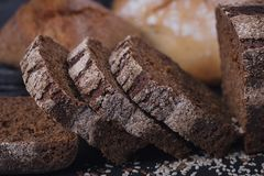 Assortment of baked bread on dark background. royalty free stock image