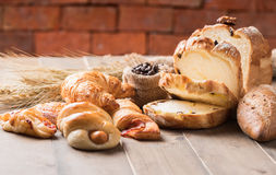 Assortment of baked bread and wheat on wood table Royalty Free Stock Photography